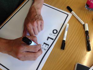 Øv dig i at tegne store bogstaver og i at trække pennen til dig/nedad (se videoerne).